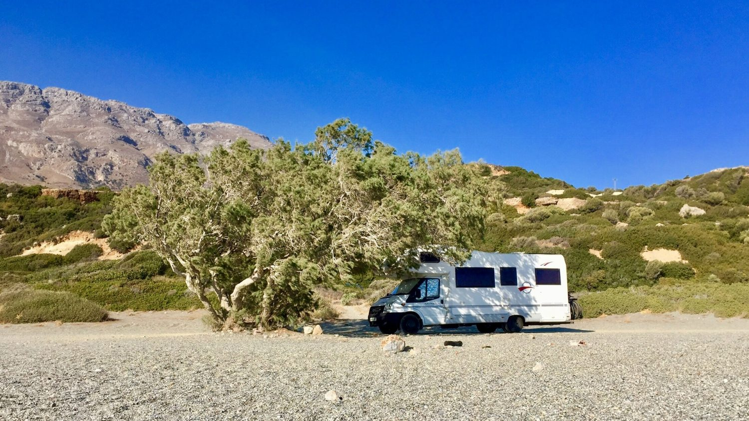 Motorhome parked up on a beach in summer under a tree.