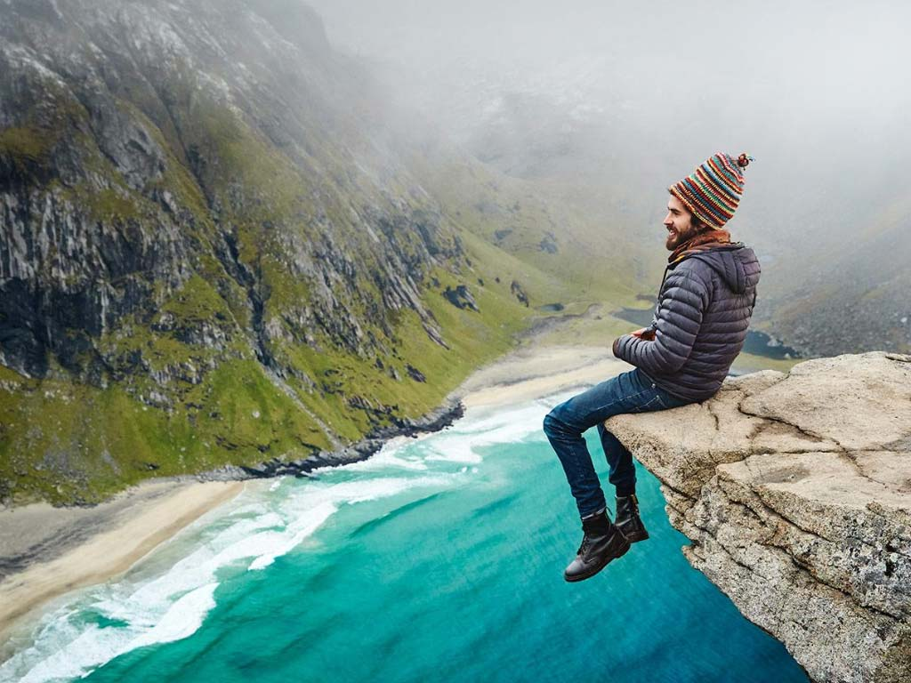 campervan man Mike Hudson from VanDog Traveller sat on the edge of a cliff in Norway